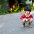 Boy drawing on asphalt - Stock Photo