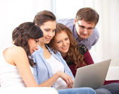 Four students and a laptop — Stock Photo