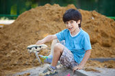 Boy pours the sand out of the shoe — Stock Photo