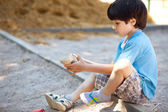 Boy shakes the sand out of the shoe — Stock Photo