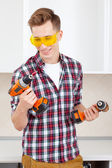 Smiling repairman in yellow safety glasses selects tool — ストック写真