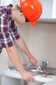 Plumber installs water tap — Zdjęcie stockowe