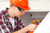 Young repairman with electric dril — Stockfoto