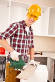 Repairman works jigsaw — Stockfoto