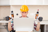 Repairman with a drill near a computer — Stock Photo