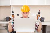 ремонтник с дрелью рядом с компьютером — Стоковое фото