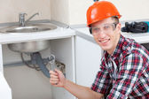 Smiling plumber near the kitchen sink — Stock Photo