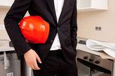 Engineer holding red helmet — Stock Photo