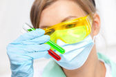 Doctor in a mask examines test tubes — Stock Photo