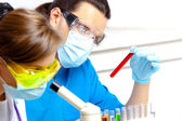 Young scientist wearing a mask examines test tube with liquid — Stock Photo