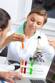 Female scientist looking at liquid in test tube — Stock Photo