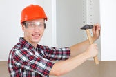 Repairman in a helmet with a hammer — Stock Photo