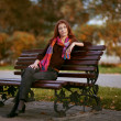 Red-haired girl on a park bench — Stock Photo