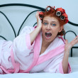 Girl in curlers on the bed, the morning — Stock Photo