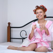 Girl in curlers on the bed - Stock Photo