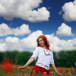 Redheaded woman in poppy field — Stock Photo