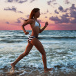 Stock Photo: Girl runs along beach