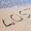 Beach with sand word lost — Stock Photo