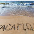 Beach with sand word vacation — Stock Photo