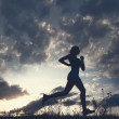 Stock Photo: Silhouette woman run under blue sky with clouds
