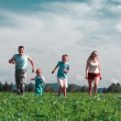 Family mother father and two child run on field — Stock Photo