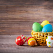 Easter color eggs in basket on wood — Stock Photo #40475605