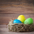 Stock Photo: Easter color eggs in nest on wood