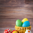 Easter color eggs in basket on wood — Stock Photo