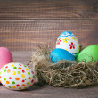 Easter color eggs in nest on wood — Stock Photo