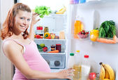 Pregnant woman and refrigerator with health food — Stock Photo