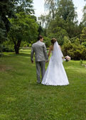 Bride and groom walking in a park — Stock Photo