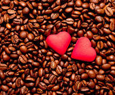Two red hearts on coffee beans — Стоковое фото