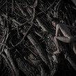 Stock Photo: Naked mis standing among roots of dead tree