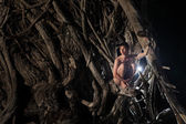 Naked man is sitting among roots — Stock Photo