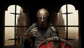 Medieval khight in the armor with the sword and helmet — Stock Photo