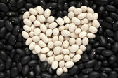 Heart shape from white haricot beans on black haricot beans back — Stock Photo