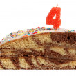 Slice of birthday cake with number four candle — Stock Photo