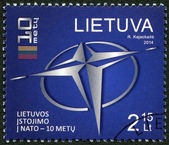 LITHUANIA - 2014: showis logo of NATO and a stylized flag of Lithuania, the 10th anniversary of the accession to NATO — Stock Photo