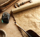 Inkwell and quill on vintage paper background — Stock Photo