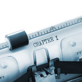 "Closeup of a typewriter with the words ""CHAPTER 1"" in blue lighting — Stock Photo"