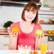 Beautiful woman holding a apple and orange - Stock Photo