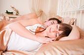 Young couple sleeping in a bed — Stock Photo