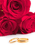 Two gold wedding bands beside a red roses. — Stock Photo
