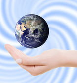 Earth surrounded by three hands. — Stock Photo
