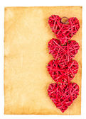 Red straw hearts on old paper — Stock Photo