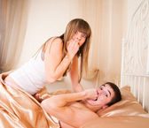 Surprised sex couple lying in bed — Stockfoto