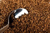 Spoon of coffee at coffe background — Stock Photo