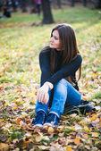 Beautiful thoughtful girl in autumn park — Stock Photo