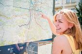 Jonge vrouw is op zoek op een kaart — Stockfoto
