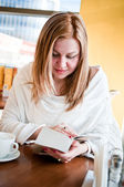 Young beautiful girl enjoying reading in cafe — Stock Photo